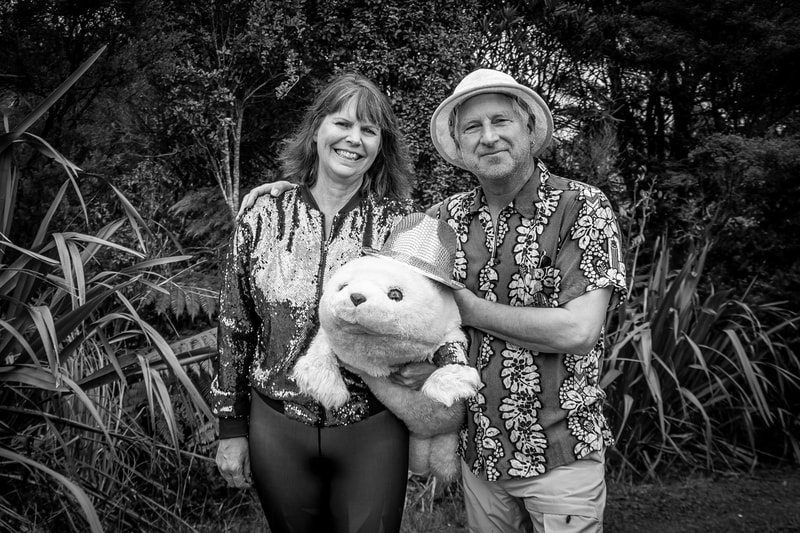 "Marianne and Clive: ""We love Te Henga/Bethells and its fantastic, quirky community. Unusual attire is not uncommon here. One of our two chickens recently died so we had to rehome the lonely survivor - Sealey is Marianne's stand-in animal companion. The lockdown means we both get to work at home; such a privilege."""